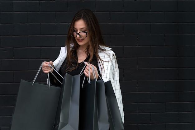 Femme d'affaires élégante avec des sacs en papier sur fond de mur noir. vendredi noir.