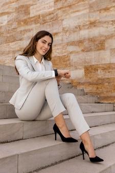 Femme d'affaires élégante avec smartwatch posant dans les escaliers à l'extérieur