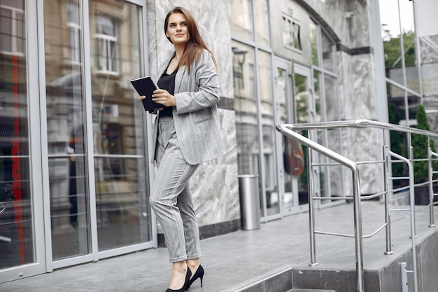 Femme d'affaires élégante travaillant dans une ville et utiliser le cahier