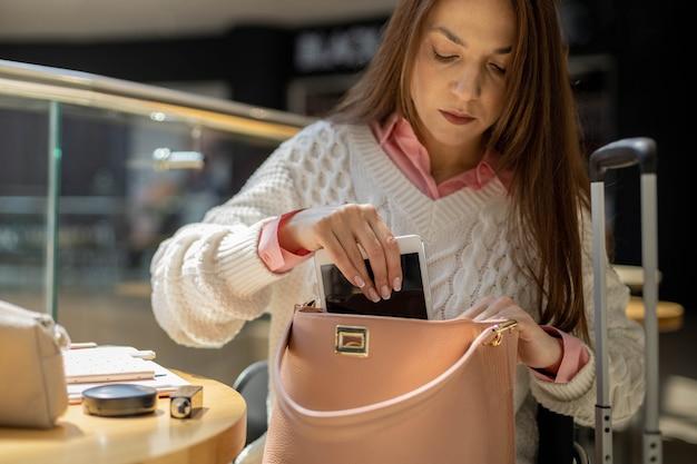 Femme d'affaires emballant des documents de cosmétiques sur tablette dans un sac à main au terminal de l'aéroport international