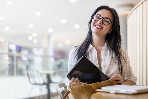 Femme d'affaires emballant des documents cosmétiques de tablette dans un sac à main
