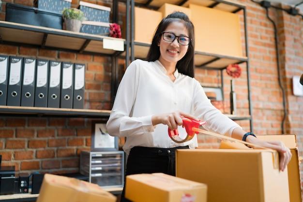 Femme d'affaires emballent des boîtes à envoyer aux clients.