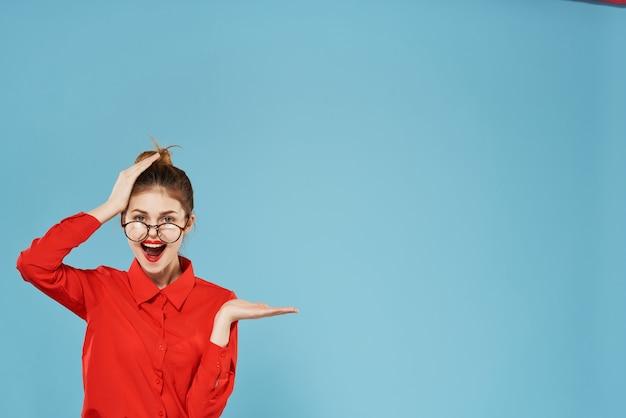 Femme d'affaires émotionnelle en chemise rouge portant des lunettes faisant des gestes avec le travail des mains