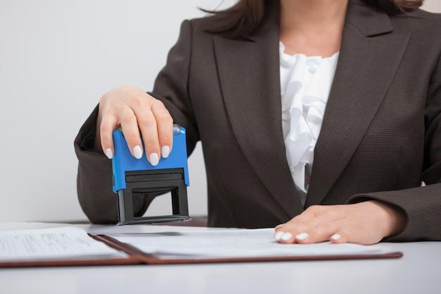 Femme affaires, employé bureau, mettre, timbre, sur, documents, bureau, concept