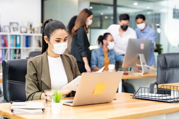 Femme d'affaires employée de bureau asiatique porte un masque protecteur pour travailler dans un nouveau bureau normal