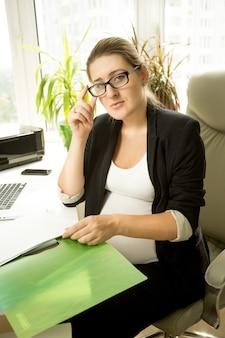 Femme d'affaires enceinte assise sur une chaise et travaillant avec des papiers