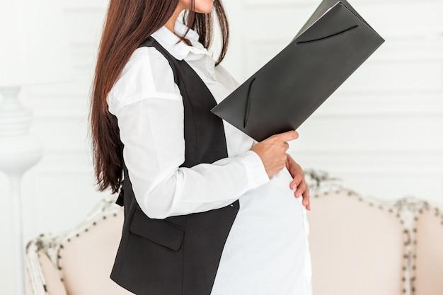 Femme d'affaires enceinte au travail dans un bureau en lisant un document.
