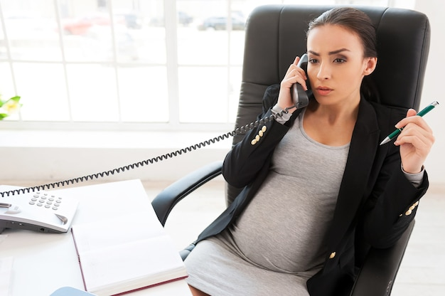 Femme d'affaires enceinte. belle femme d'affaires enceinte parlant au téléphone alors qu'elle était assise sur son lieu de travail au bureau