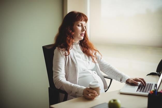 Femme d'affaires enceinte utilisant un ordinateur portable tout en prenant un café
