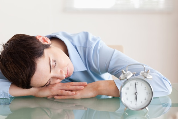 Femme d'affaires endormie avec sa tête sur le bureau à côté d'un réveil
