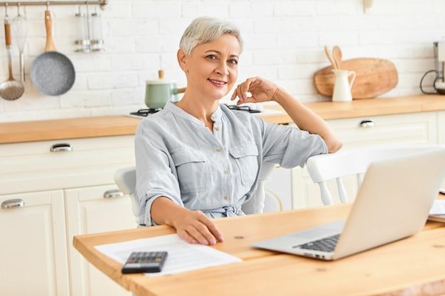 Femme d'affaires énergique moderne d'âge mûr assis à table à manger, prendre le petit déjeuner et vérifier le courrier électronique à l'aide d'un ordinateur portable. élégant pigiste senior travaillant à domicile sur ordinateur portable