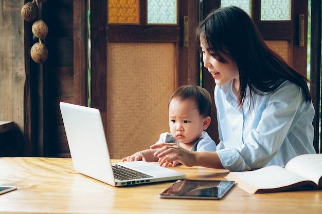 Femme d'affaires enseignant son fils avec ordinateur portable, tablette et livre, l'enseignement à la maison.