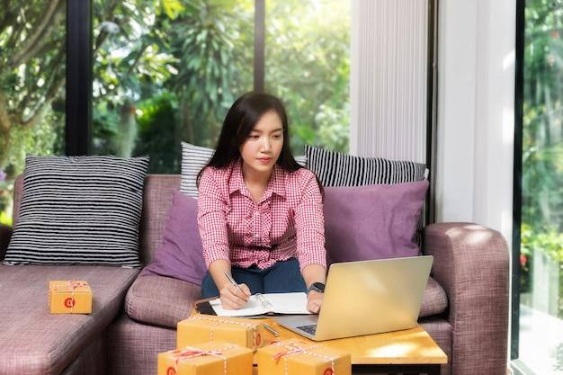 Femme d'affaires entrepreneur prospère avec vente en ligne et expédition de colis dans son bureau à domicile. femme vérifiant la commande sur ordinateur portable et ordinateur portable.