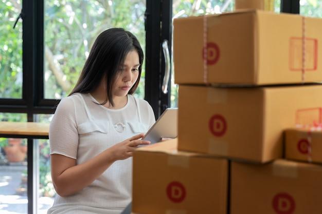 Femme d'affaires entrepreneur avec vente en ligne et expédition de colis.