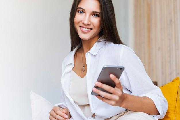 Femme d'affaires est assise à table devant un ordinateur portable, écrit un message à l'aide d'un smartphone, effectue une correspondance commerciale au travail. belle fille brune utilise des gadgets pour le travail. travail à distance en ligne.