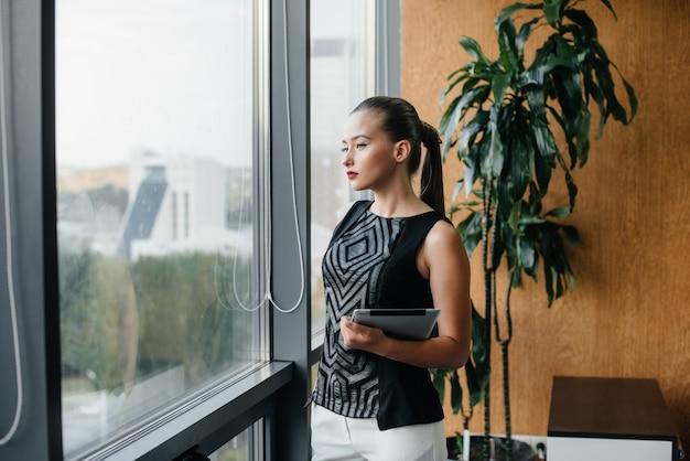 Femme d'affaires est debout dans le bureau près de la fenêtre et étudie les documents. affaires, finance, avocat