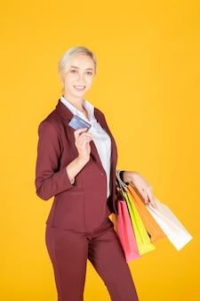 Femme d'affaires est heureuse de faire du shopping en studio fond jaune