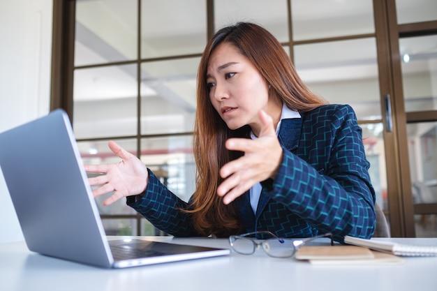 Une femme d'affaires est stressée en travaillant sur un ordinateur portable au bureau