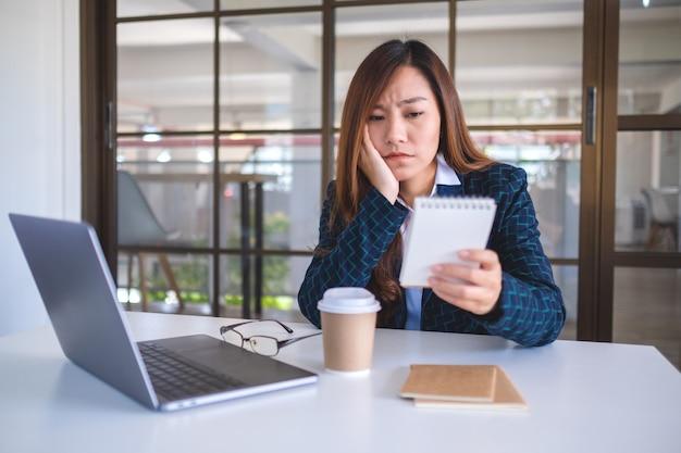 Une femme d'affaires est stressée en travaillant et en regardant un document au bureau