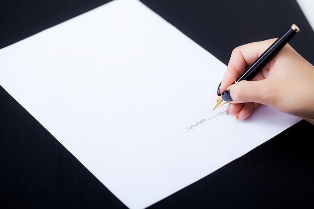 Femme d'affaires est en train de signer un contrat