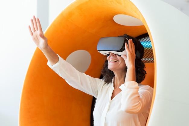 Femme d'affaires étonnée dans un casque vr touchant l'air