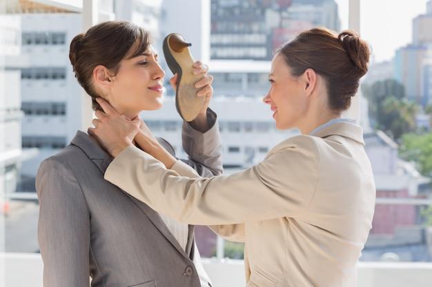 Femme d'affaires étrangler une autre qui défend avec sa chaussure