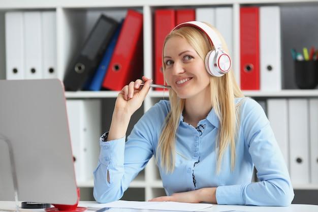 Femme d'affaires étudiant en ligne. il écoute la conférence, tenant un stylo près du menton et souriant