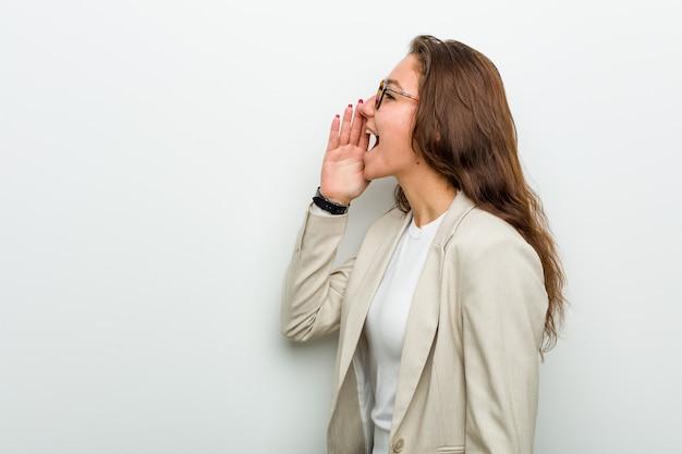 Femme d'affaires européenne jeune en criant et en tenant la paume près de la bouche ouverte.