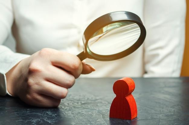 Femme d'affaires examine la figure d'un homme rouge