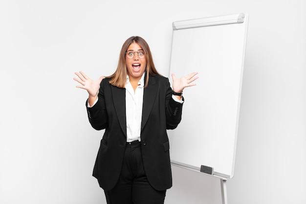 Femme d'affaires excitée devant un tableau blanc
