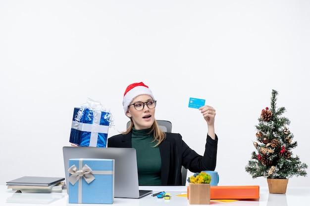 Femme d'affaires excitée positive avec chapeau de père noël et portant des lunettes assis à une table tenant un cadeau de noël et une carte bancaire sur fond blanc