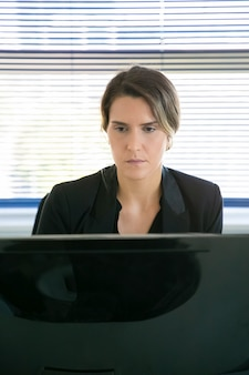 Femme d'affaires expérimentée assise dans la salle de bureau et regardant l'écran. employé de bureau joli contenu caucasien travaillant sur un projet via ordinateur. concept d'entreprise, de technologie numérique et de société