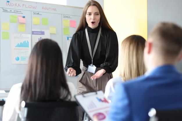 Femme d'affaires expliquant des informations aux auditeurs sur un tableau noir