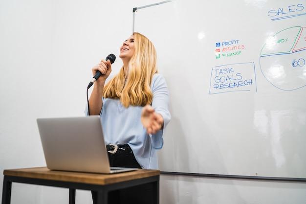 Femme d'affaires expliquant le plan de travail en conférence.