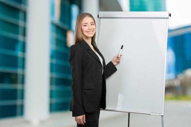 Femme d'affaires expliquer au tableau blanc