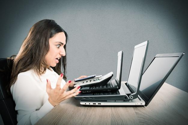 Femme d'affaires avec une expression de colère et a souligné devant trois ordinateurs portables