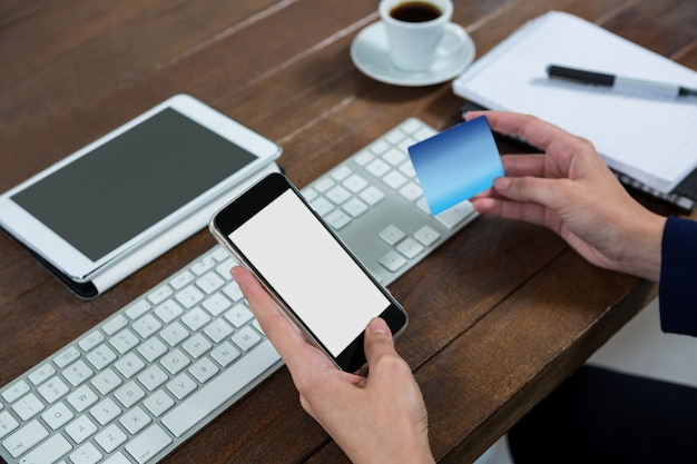 Femme d'affaires faisant des achats en ligne sur téléphone mobile