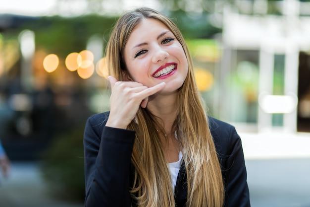 Femme d'affaires faisant un appel moi signe et souriant