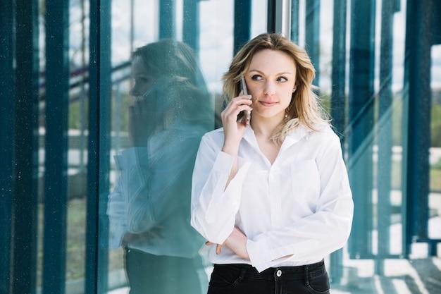 Femme d'affaires faisant un appel téléphonique à côté de windows
