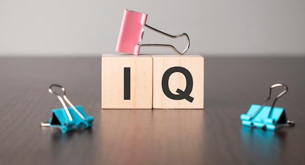 Une femme d'affaires a fait le mot qi avec des blocs de construction en bois.