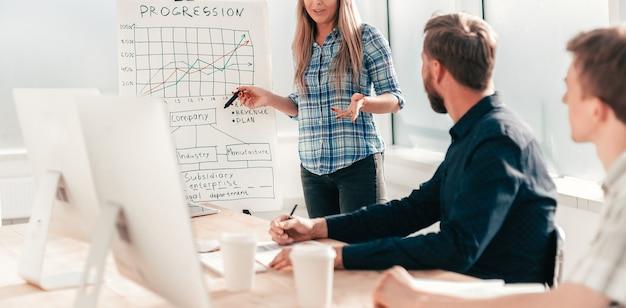 Une femme d'affaires fait un rapport à l'équipe commerciale lors d'une réunion au bureau. photo avec espace copie