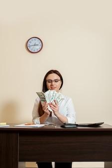 Femme d'affaires avec des fans d'argent dans les mains