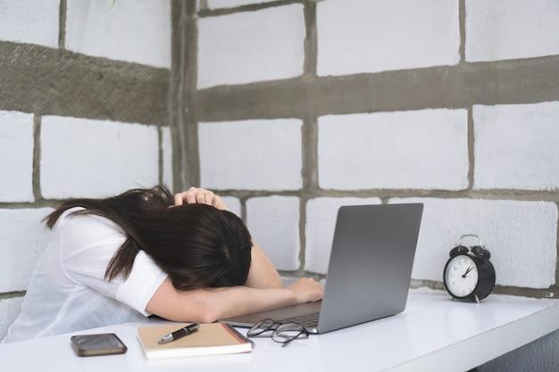 Femme d'affaires fatigué, dormant sur un bureau blanc devant l'écran d'ordinateur portable ouvert.
