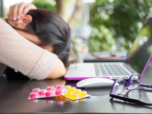 Femme d'affaires fatigué a mal à la tête du syndrome de bureau après de longues heures de travail sur ordinateur.