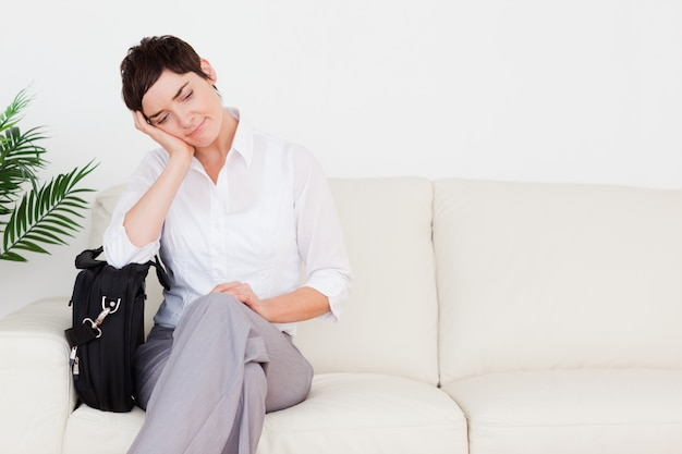 Femme d'affaires fatigué avec un papier et un sac