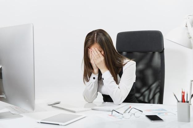 Femme d'affaires fatiguée, perplexe et stressée aux cheveux bruns en costume assise au bureau, se couvrant le visage avec les mains, travaillant sur un ordinateur contemporain avec des documents dans un bureau léger