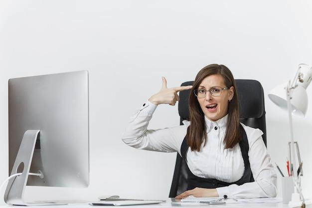 Femme d'affaires fatiguée, perplexe et stressée en costume assise au bureau, travaillant sur un ordinateur contemporain avec des documents, mettant sa main à la tête comme un pistolet pour tirer au bureau