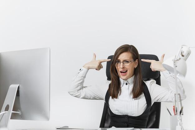 Femme d'affaires fatiguée, perplexe et stressée en costume assise au bureau, travaillant sur un ordinateur contemporain avec des documents, mettant ses mains sur la tête comme un pistolet pour tirer au bureau