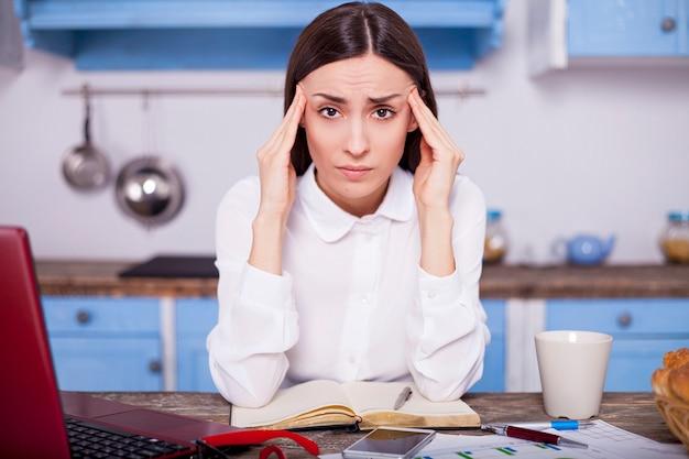 Femme d'affaires fatiguée et stressée est inquiète à la recherche dans l'appareil photo tout en travaillant sur un ordinateur portable à la maison