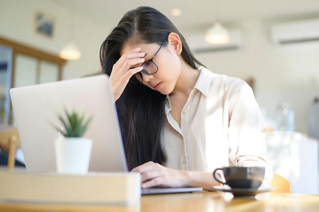 Une femme d'affaires fatiguée et stressée avec des maux de tête d'utiliser un ordinateur portable dans un café
